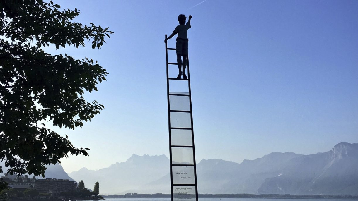 Boy high atop a ladder without support